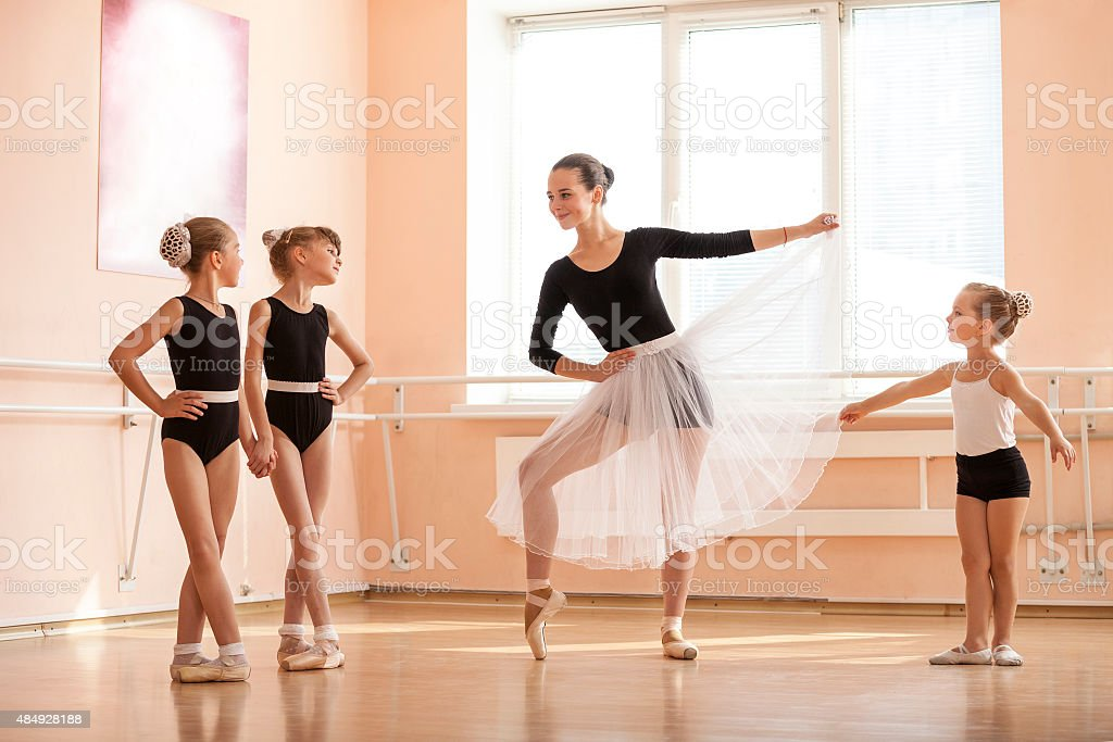 Young girl warming up and talking to younger dance students stok fotoğrafı