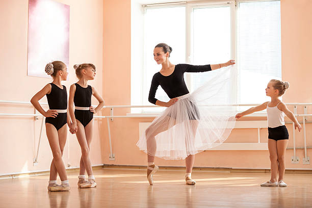 Young girl warming up and talking to younger dance students stock photo