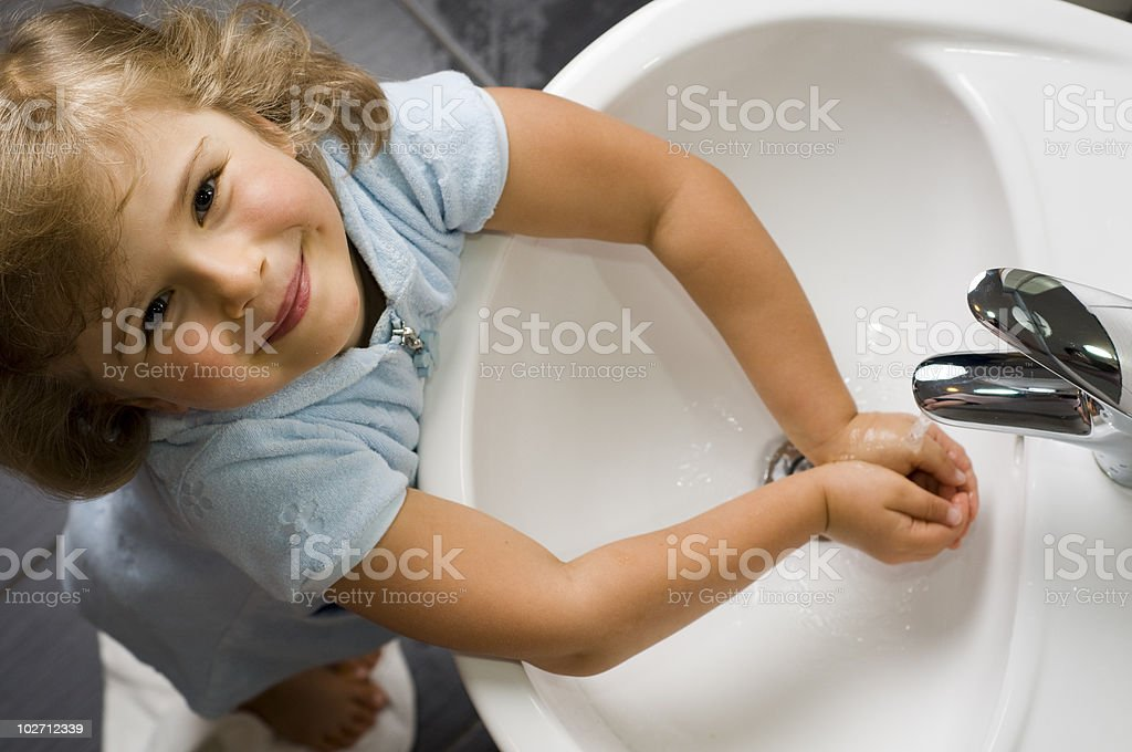 Young girl washing hands while looking up stock photo