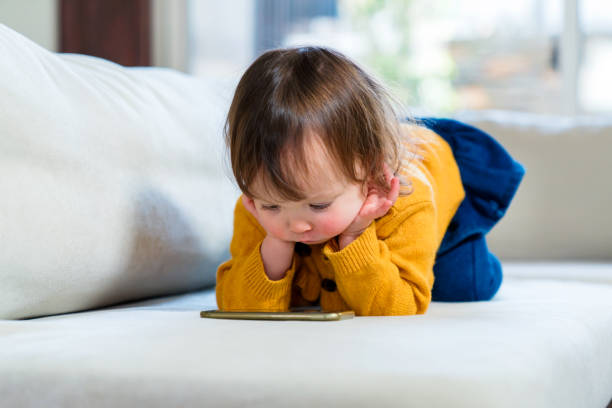 Young girl watching TV on a smartphone stock photo