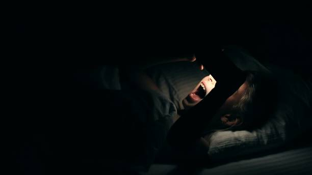 Young girl watching video on smartphone lying down in bed. Night shot in bedroom with white girl using cell phone for watching movie or video channel from internet. stock photo