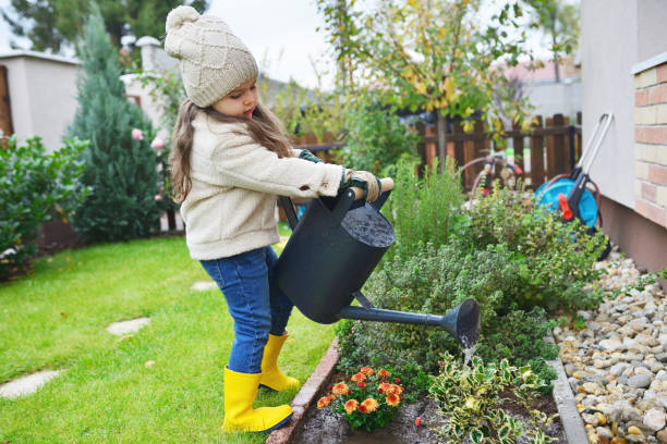 Young girl watering flower stock photo
