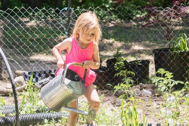Young Girl Watering the Garden 1 – zdjęcie