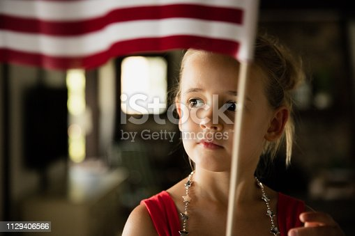 96695299 istock photo Young Girl Waving American Flag 1129406566