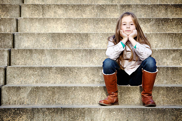 A young girl wearing a boots sitting on the stairs stock photo