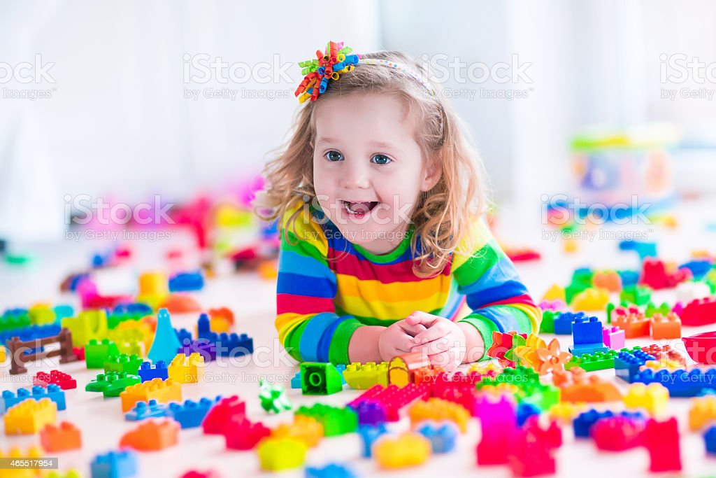 A young girl wearing a colorful shirt playing with blocks stock photo