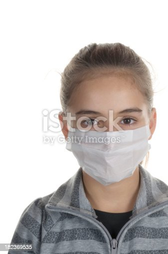 Close-up of young girl wearing a mask on white background
