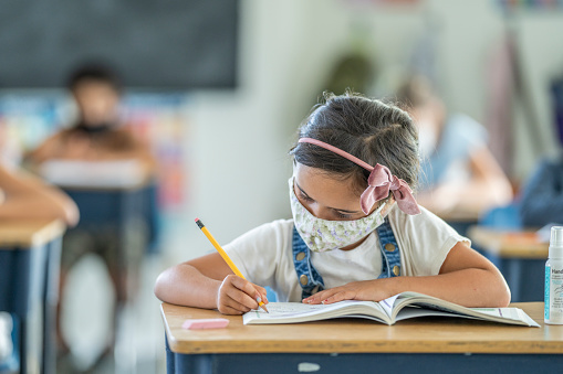 6 year old girl wearing a reusable protective face mask while working at her desk in school.
