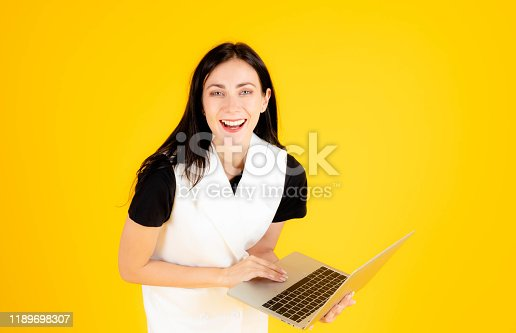 1176252245 istock photo A young girl wearing a white dress and a black inner shirt is laughing happily while holding a laptop on a yellow background for the banner. 1189698307