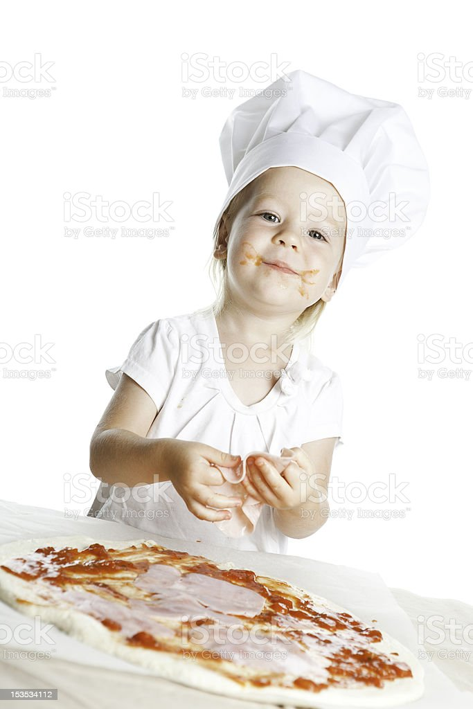 Young girl wearing chefs hat, making pizza stock photo
