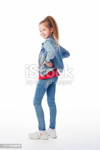 Young girl wearing denim coat, red shirt, jeans and white sneakers looking backwards, arms on hips