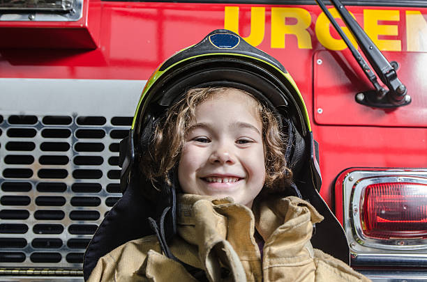 Young girl wearing fireman coat and helmet ストックフォト