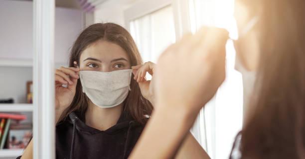 jong meisje dat medisch beschermend gezichtsmasker draagt dat spiegel kijkt blijf thuis - mirror mask stockfoto's en -beelden