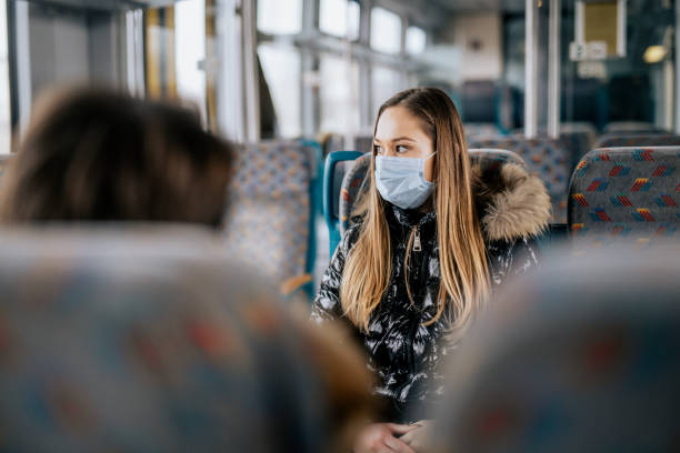 Young girl wearing protective face mask sitting on a train stock photo