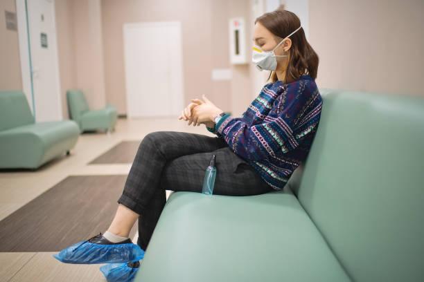 Junges Mädchen trägt Schutzmaske und mit Antiseptikum für Hände Desinfektion in der medizinischen Klinik – Foto