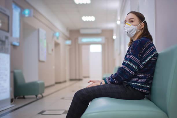 Junges Mädchen trägt Schutzmaske in der medizinischen Klinik – Foto