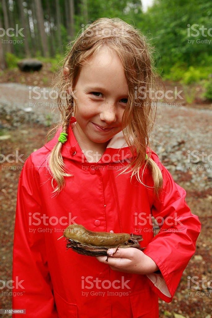 Young girl wearing red raincoat holding a large banana slug stock photo