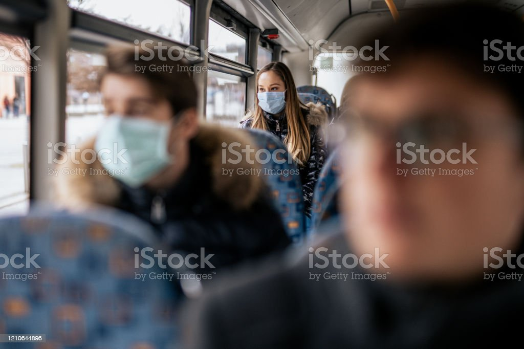 Young girl wearing sterile face mask using a public transport Young girl is wearing sterile face mask because of the new Coronavirus COVID-19. She is sitting on a bus. She is looking outside the window. Adult Stock Photo