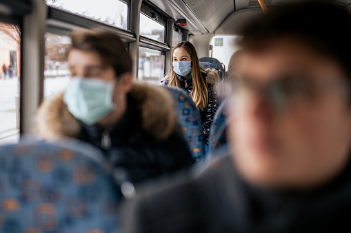 Young girl is wearing sterile face mask because of the new Coronavirus COVID-19. She is sitting on a bus. She is looking outside the window.