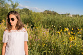Young 13 year old girl wearing sunglasses, blue jeans, white shirt in field with white and yellow flowers