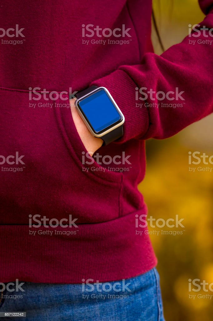 Young girl wears smart watch with hand in pocket. Focus on smart...