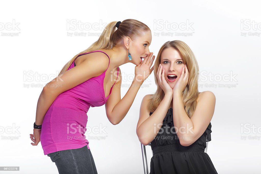 Young girl whispers a secret royalty-free stock photo