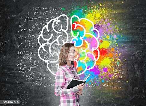 istock Young girl with a book and large brain 650667520