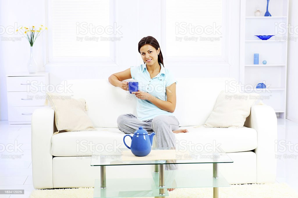 Young girl with a cup of coffee enjoys at home. royalty-free stock photo