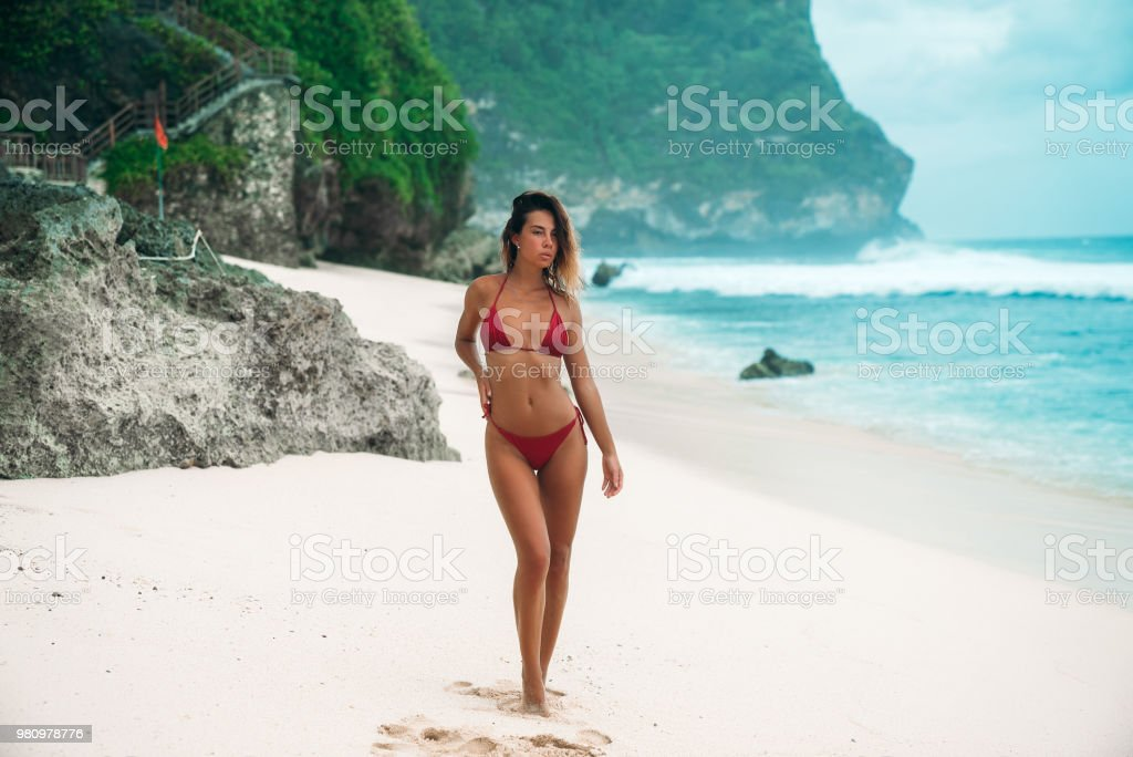 e0284e86e23 멋진 몸 가진 어린 소녀 바다 근처 하얀 모래 해변에서 휴식. 빨간 수영복 일광욕
