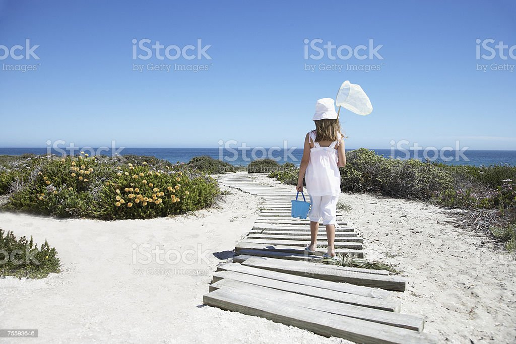 A young girl with a net walking to the beach royalty-free stock photo