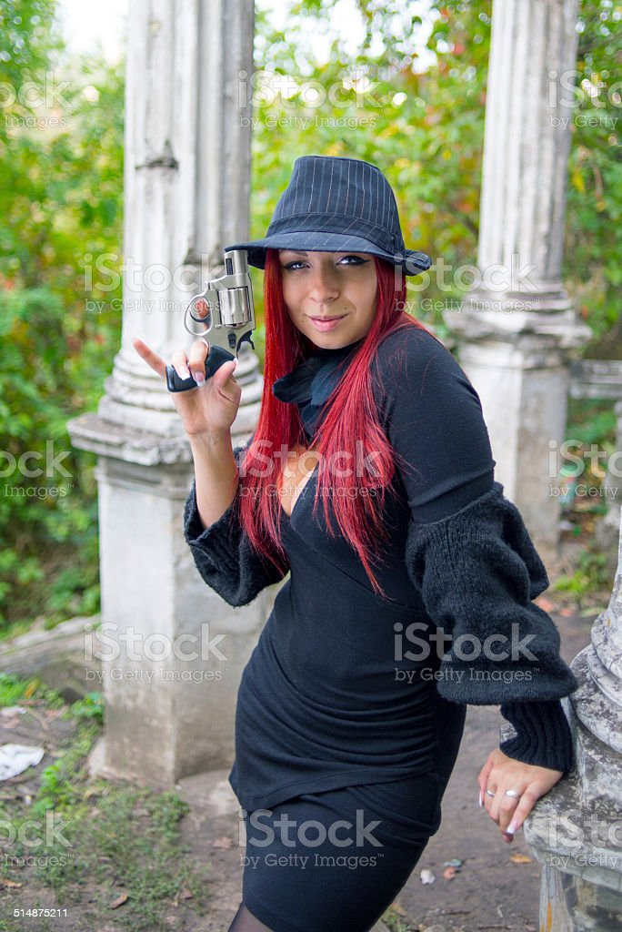 Young girl with a pistol in hands stock photo