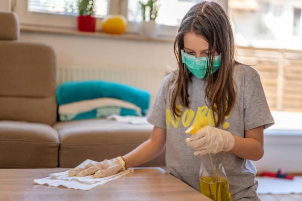 Junges Mädchen mit einer schützenden Gesichtsmaske und Schutzhandschuhen reinigung den Tisch zu Hause – Foto