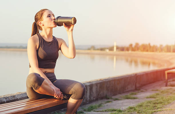 young girl with a shaker water outdoors - protein stock photos and pictures