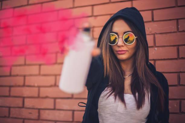 Chica joven con un spray puede - foto de stock