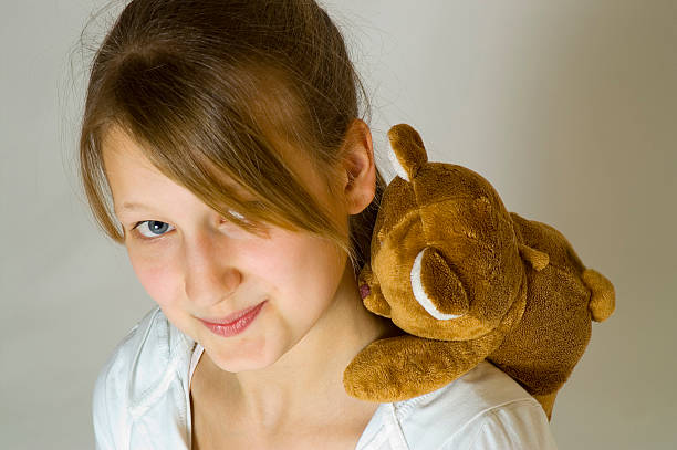 Young girl with a teddy bear stock photo