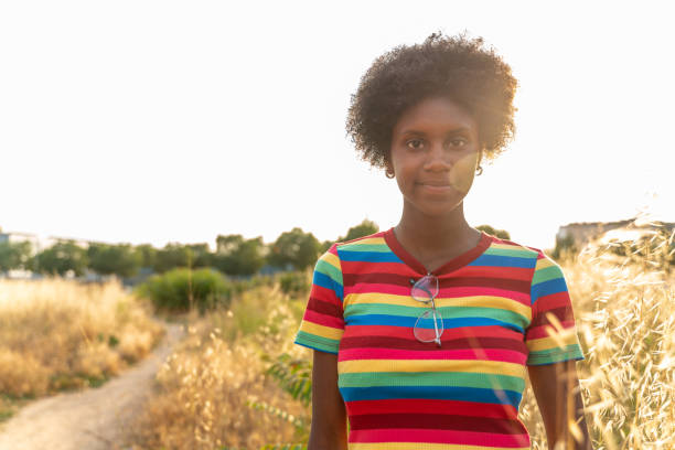 Young girl with afro hair, relaxing in a field at summer stock photo