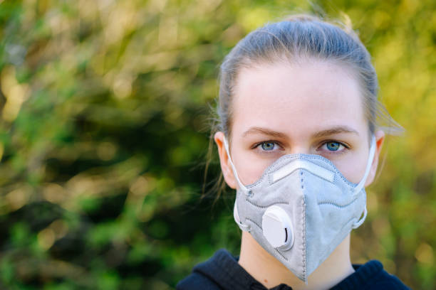 young girl with anti-virus anti-smog mask on her face stock photo