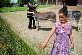 In this special center, a shelter for battered and abandoned animals, they are trained to be in contact with neuro atypical people, so they can comfort each other. A young autist girl is playing with grass under the supervision of her mother. Horizontal waist up outdoors shot with copy space.