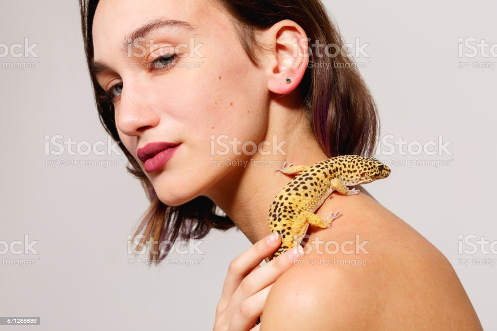 Young girl with bare shoulders on a gray background. An iguana gecko crawls over her shoulders. Inside. stock photo