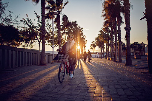 Young girl with bicycle is enjoying the sunset on the beach boulevard