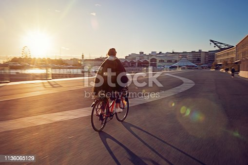 Young girl with bicycle is enjoying the sunset on the beach