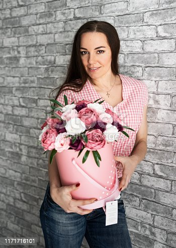 A young girl with blond hair holds and hugs a large box with white and pink roses against a gray wall. Portrait.
