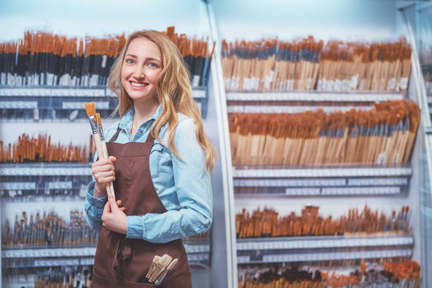 Young girl with brushes in the store stock photo
