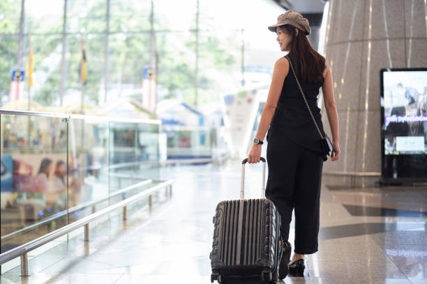 Young girl with cabin luggage at Malaysia airport ready to travel Young girl with cabin luggage at Malaysia airport ready to travel kuala lumpur airport stock pictures, royalty-free photos & images