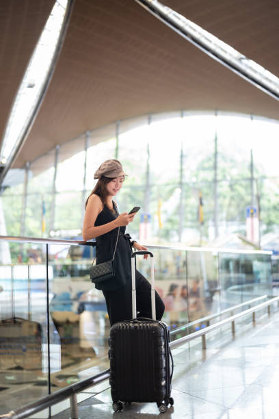 Young girl with cabin luggage using phone in malaysia airport Young girl with cabin luggage using phone in malaysia airport kuala lumpur airport stock pictures, royalty-free photos & images