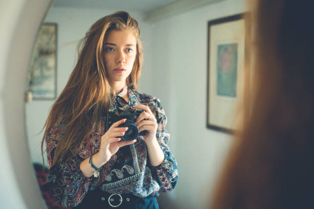 Young girl with camera in hand stands in front of the mirror, takes a selfie stock photo