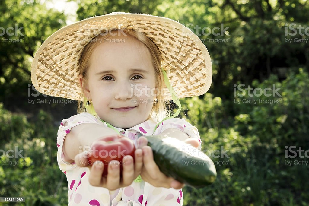 Young girl with cucumber in the garden royalty-free stock photo