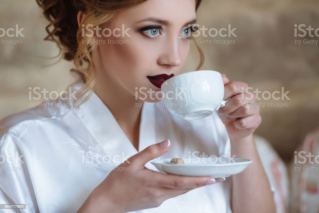 A young girl with curls and red lips drinks coffee in a silk dressing gown. A close-up of the girl is about to take a sip from the cup, holding the saucer royalty-free stock photo