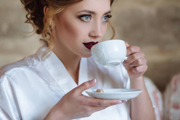 ein junges mädchen mit locken und rote lippen trinkt kaffee in einen seidenen morgenmantel. eine nahaufnahme des mädchens soll einen schluck aus der tasse, halten die untertasse - festliche kleider kindermode stock-fotos und bilder