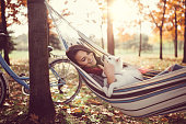 Woman with doggy relaxing in the autumn park